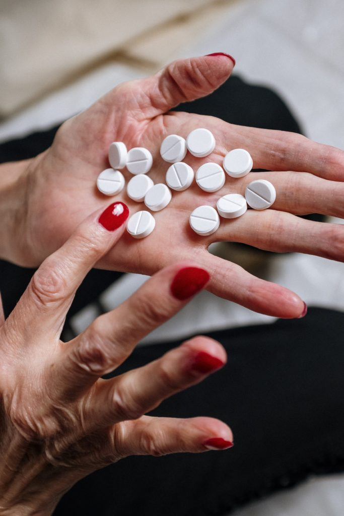 An AgeWell community member counting prescription tablets in her hand